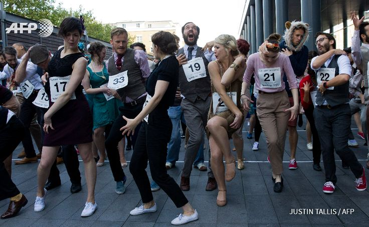 UNITED KINGDOM, London : Performers dance the Charleston during an  attempt to break the record for the world's largest Charleston dance, at  Spitalfields Market in London on October 11, 2015. With 977  participants, today's attempt broke the previous record of 503 people,  set in Bexhill, southern England on July 18, 2015.    AFP PHOTO / JUSTIN  TALLIS