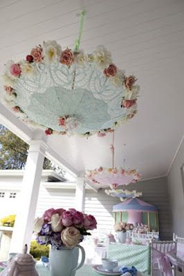 Lace umbrellas with pearls and flowers hanging outside