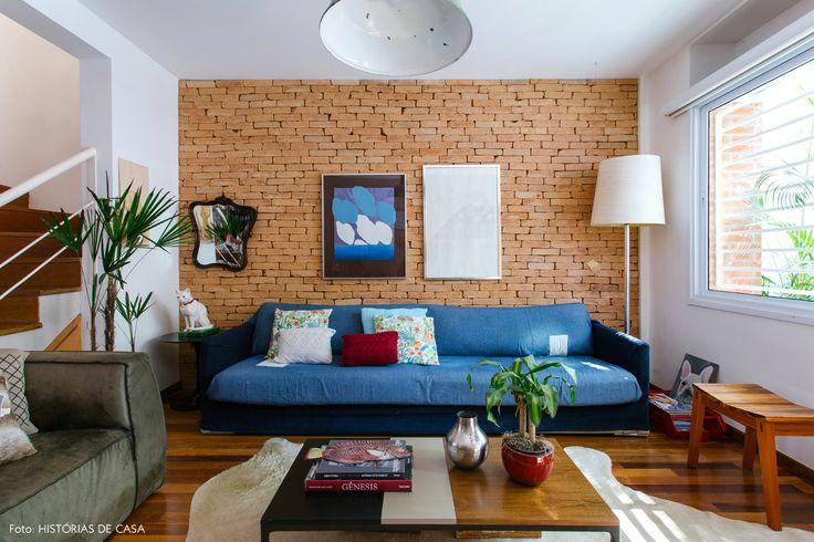 Sala de estar de casinha de vila tem parede de tijolinhos, sofá azul jeans e móveis de madeira.