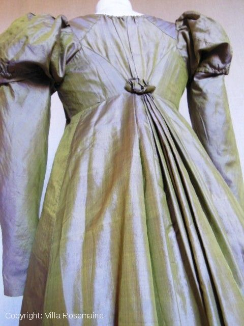 Lovely dress dating from the period of the First French Empire in taffeta silk changing from green yellow bronze to purple and deep violin. Nice finishing sewing by hand, this high-waisted dress closes at the front with two slides at the neckline and under the chest, back cutting in diamond ending with an elegant rose, ancestor of the pet-en-l'air.