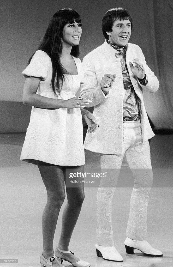 Full-length image of married American singers Cher (left) and Sonny Bono (1935 - 1998) of the pop duo Sonny and Cher performing on 'The Carol Burnett Show'. Sonny and Cher are wearing costumes with matching print.