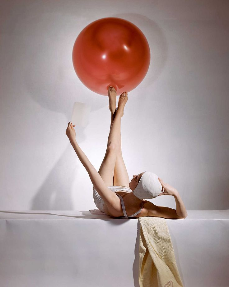 """Horst P. Horst photographed """"Balance"""", showing a lying model in a white bathing suit and cap balancing a red beach ball on her feet, for the Vogue in 1941."""