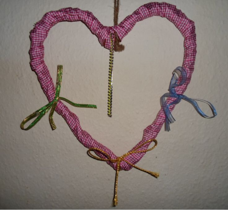 A wooden heart decorated with red/white ribbon, three bows and a yellow chain.