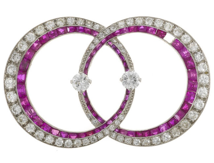 An art deco diamond and synthetic ruby double circle brooch, circa 1930  estimated total diamond weight: 1.80 carats; mounted in platinum; length: 1 5/8in