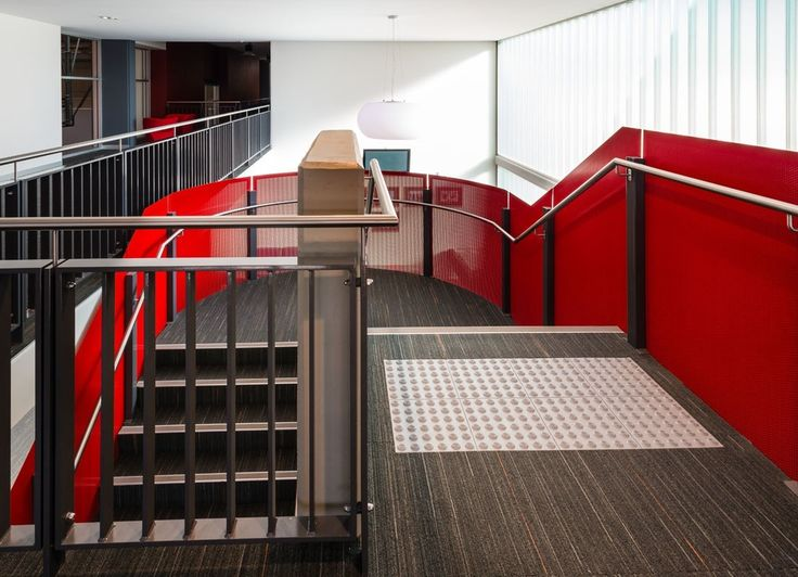 Red perforated metal #balustrade is used throughout the #blacktowntenniscentre to provide visual interest and contrast, creating a vibrant and modern #sportingvenue #arrowmetal #perforatedmetal #publicvenue #publicspace #interiordesign #metalstaircase #modernstaircase #curvedstaircase #publicproject