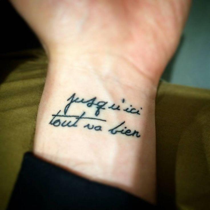 "Wrist tattoo saying ""Jusqu'ici tout va bien"", which means ""So far, so good""."