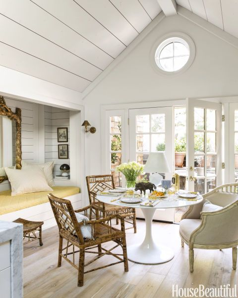 Dhong centers the breakfast area on a Saarinen-style table, under a nautical porthole that adds luminosity. A Jules armchair by Bliss Home & Design adds variety to the seating arrangement. The banquette doubles as a sleeping alcove — all the pieces exsist on a distressed white-oak floor.