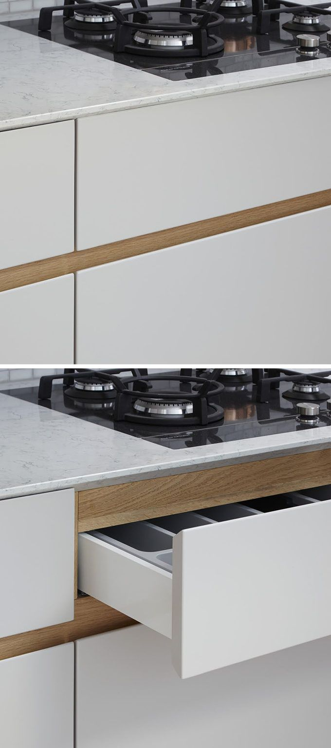 Kitchen cabinets without hardware is a growing trend. The kitchen seen here, designed by Fraher Architects for a home in London, is an example of that trend. Working together with their in-house joinery team, the designers included a recessed finger detail made from European oak, to make it easy to open the drawers and cabinets. Here you can see how the recessed finger detail works when opening..