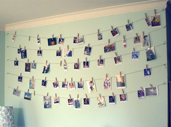 Photos hanging on the wall with clothes pins