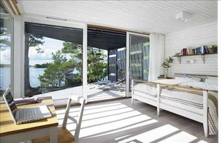 Skuggspel i sovrummet. Golven är vitlaserade och tak och väggar i vitmålad råspont. Säng, skrivbord och stol av Nirvan Richter för Norrgavel, små sänglampor från Flux, och i taket vita kubformade strål-kastare från Isola