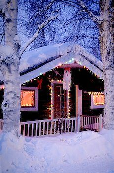 Snow Covered Log Cabin With Christmas Lights