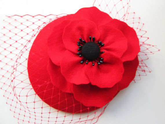 A gorgeous poppy bloom nestles on a bed of veiling to create an elegant yet eye-catching cocktail hat. The hat is handmade from 100% wool felt