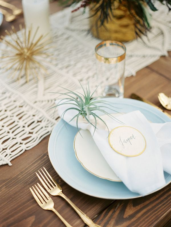 A midcentury-modern-meets-bohemian place setting with gold flatware and an air plant   Photo by Emilie Anne Photography   Event design by Two Be Wed