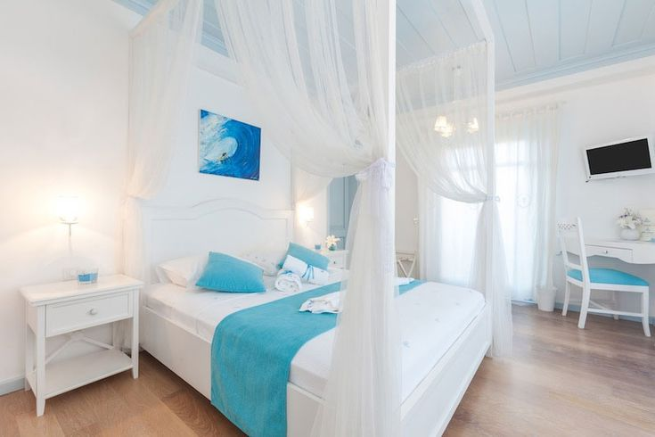 white wood furnishing and various blue textiles and accessories in the rooms of Alura hotel