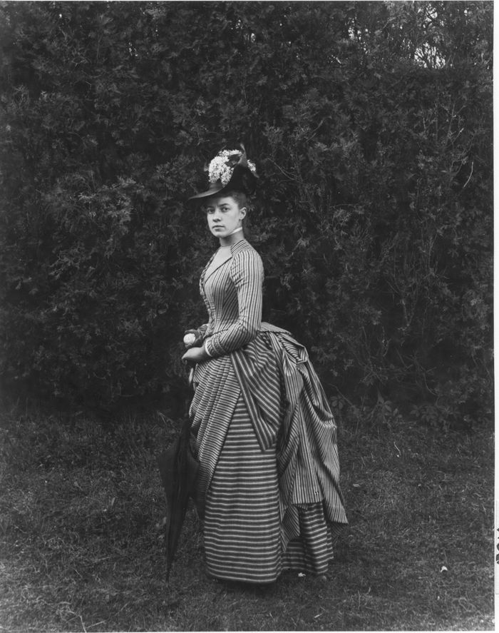 Twenty-two-year-old Miss E. Alice Austen poses in her Sunday best - a smart overskirt and a hat decorated with white lilacs. She holds a parasol and a silver change purse. Photo taken in June 1888 by Captain Oswald Muller.