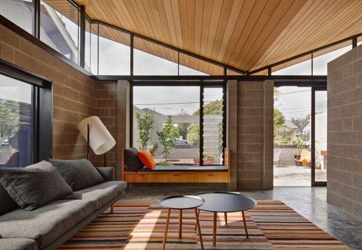 Il living, illuminato da ampie vetrate e definito dal soffitto in legno di cedro, affaccia sul cortile, vero cuore del progetto