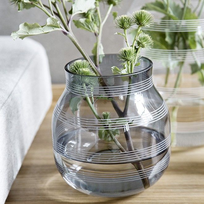 Discover the beautiful glass vase in the Omaggio range. On the new small steel vase, the stripes are narrower than usual. The combination of this graphic detail with the glass succeeds in conveying a delicate design expression with an elegant lightness. The translucent material brings a feeling of both life and luminosity, whenever the candle's glow shines through the vase, no matter where it stands.
