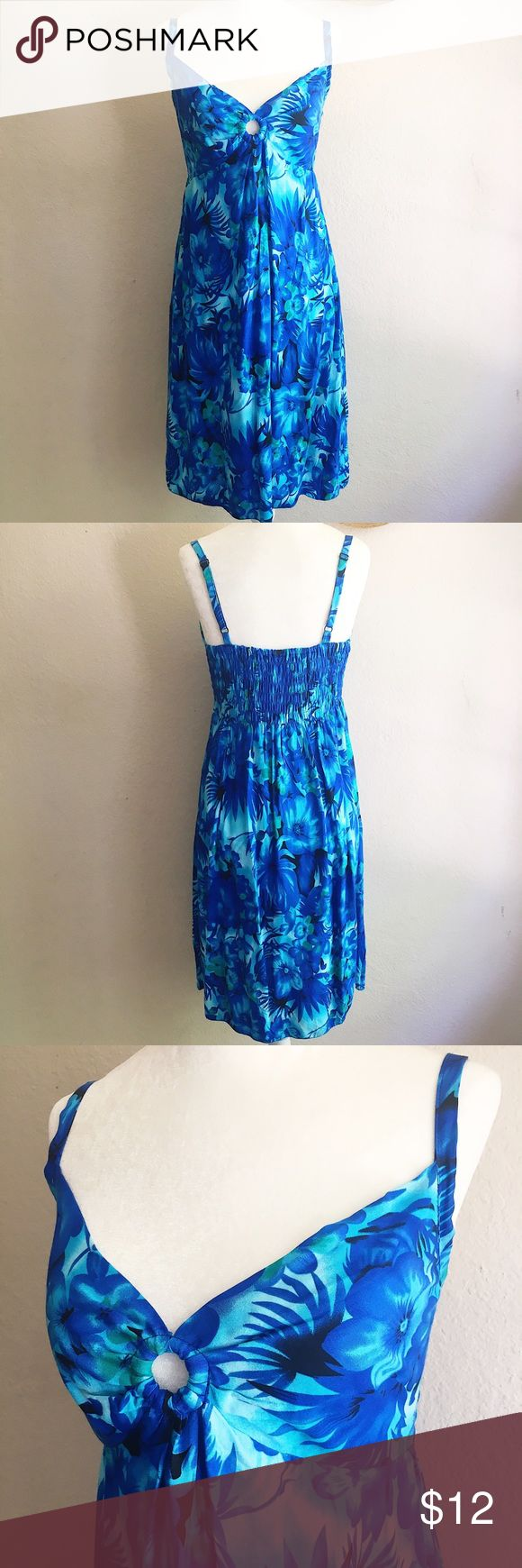 Tropical Blue Beach Dress Island Planet brand bright blue floral beach dress with adjustable spaghetti straps, ring detail at bust, and smocked back. It's a one size fits all, but fits most like a small (the dress form in the pics is a size small). 100% rayon. Ends at or just below the knee. Machine wash, lay flat to dry. In excellent used condition. No stains, holes, pilling, or fading. Swim Coverups