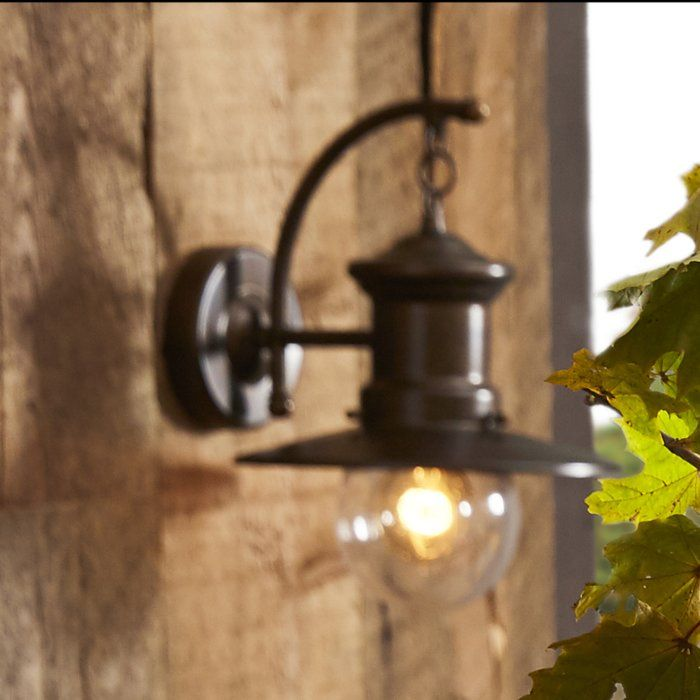 Light up your backyard in a distinctive style with this 1 Light Outdoor Wall Lantern. It is made from stainless steel and glass that makes it strong and long lasting. This wall lantern has a hazelnut bronze finish that lends a stylish appeal to your outdoors. The modern wall lantern accommodates a 60W incandescent bulb and works on 120 volts power. This wall lantern is hardwired and requires assembly. This 1 Light Outdoor Wall Lantern is title 24 compliant and is ideal to be fixed on damp…