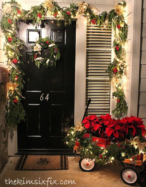 Beautiful traditional front porch.. Love the lighted garland and the old red wagon full of poinsettias