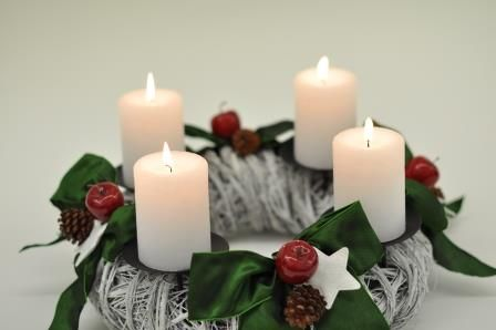 advent wreath made of white meadow, lush green ribbons and snow-white vintage candles