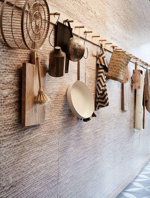 Op de lange wand zit behang gemaakt van een uitvergrote foto van grof geweven linnen.