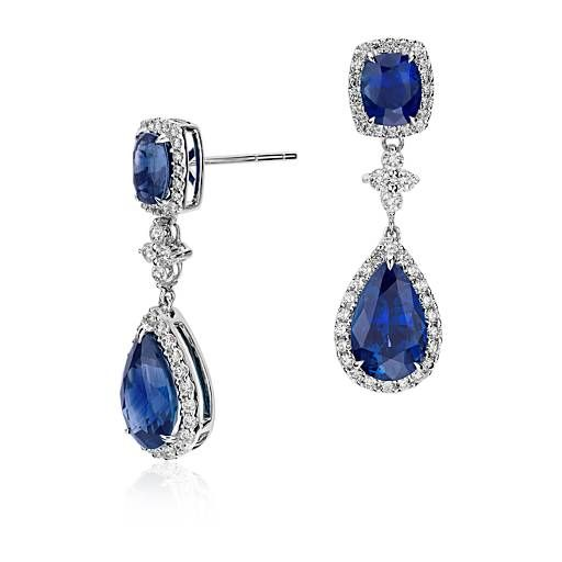 Vibrant color is captured in these exquisite gemstone and diamond earrings, showcasing 8.21 carats of  blue sapphires highlighted by a dazzling halo of pavé-set diamonds framed in 18k white gold.