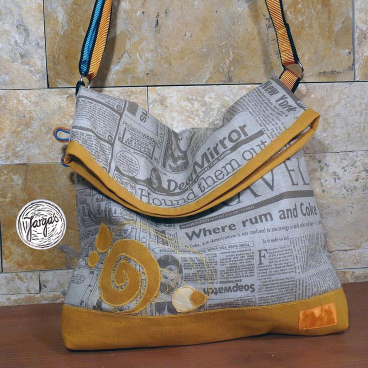 Bag inspired by climbing. Fabric is mostly grey with newspaper design.