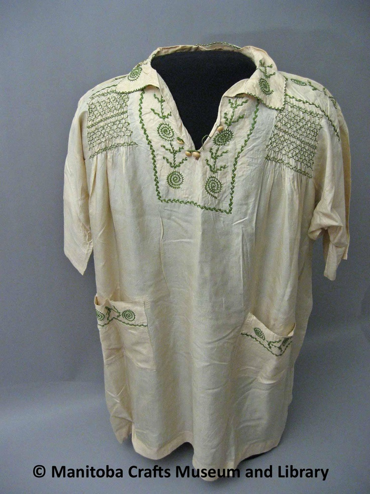 Pongee silk with V neck and 4 buttons. Embroidery on collar and yoke. Two pockets with same embrodiery (leaf and spiral) embroidered across back shoulder. Smocking on front shoulders and middle of back.