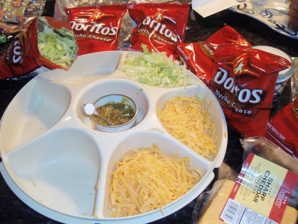 WALKING TACOS! Crunch up a bag of Doritos and add to the bag ground beef, refried beans, cheese, salsa, sour cream, and a fork. Best teen party meal EVER. food-and-drink
