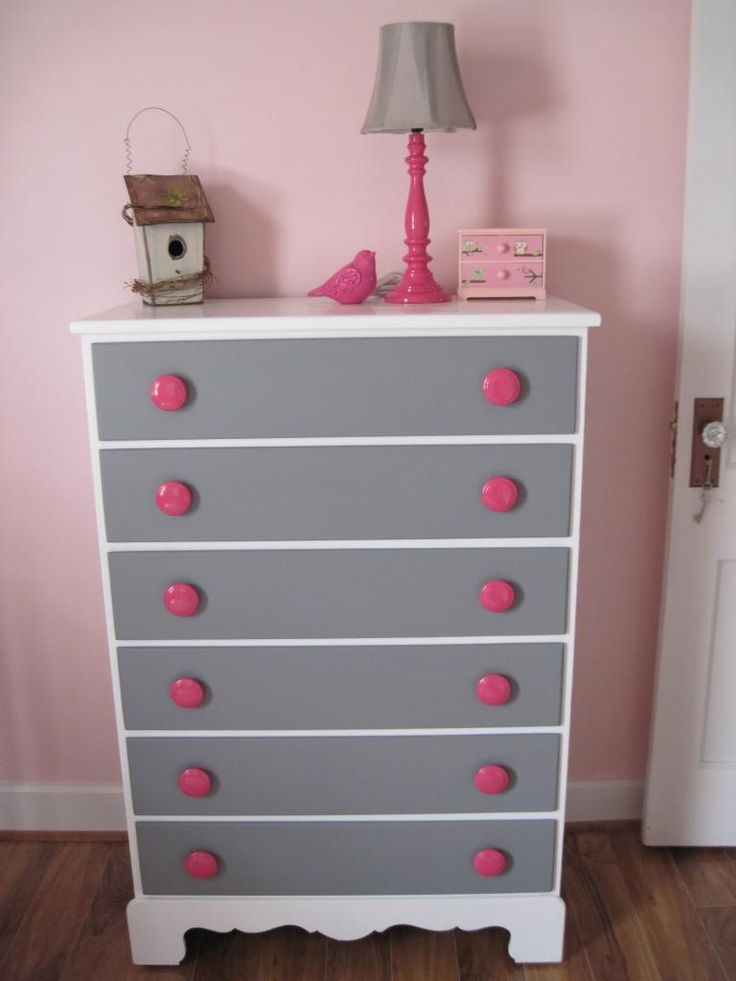 Painted chest of drawers with a pink lamp and grey lamp shade.