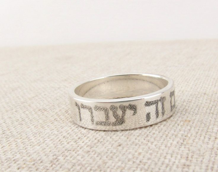 "A beautiful sterling silver band with the Hebrew characters for ""This too shall pass"" inscribed on the exterior. We can also engrave inside if you would like. The ring is 5mm wide and made of solid st"