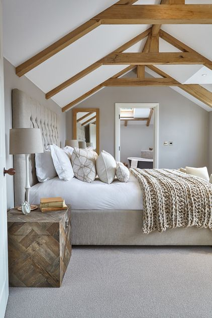 The weathered palette of pale biscuit for the walls and floor here unifies the awkward angles of the bedroom with ease, while the vast linen-buttoned headboard, chunky knit throw and crisp cotton bedding create a balance of textures that is elegant yet inviting.