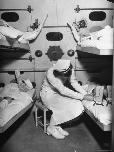 Nurse Tending 4 Young Polio Patients.....in the hyperbaric chambers....full of oxygen to treat the polio victims!