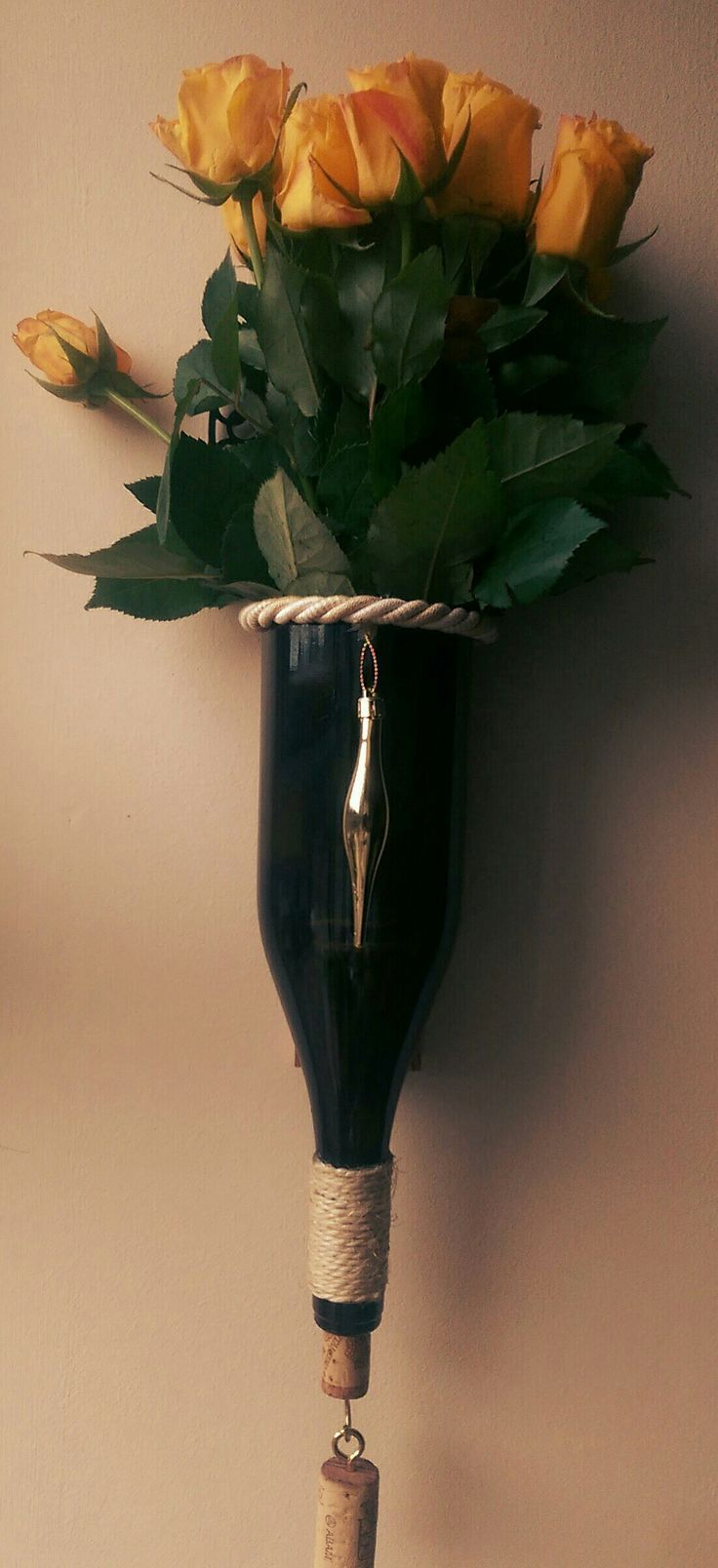 Cut wine bottle, decorated with cord and gold bauble. Mounted to wooden plinth and used as a vase with freshly cut roses!
