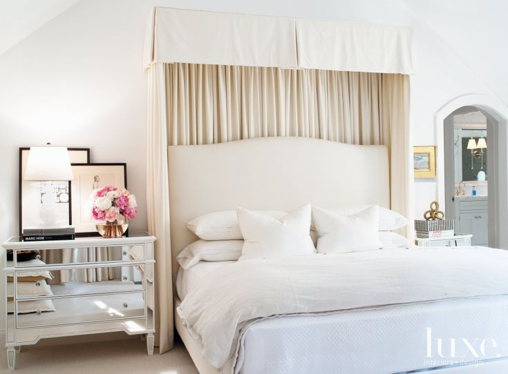 The master bedroom's custom canopy and linens are by Frederick. A Sandy Chapman gourd lamp from Visual Comfort adorns a mirrored nightstand by Global Views.