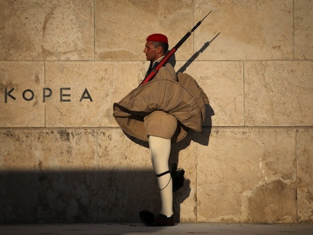Rain, snow-- even wind-- will not defeat the trusted and resilient guards at the Tomb of the Unknown Soldier in Athens, known as the Evzone. The khaki variation of the traditional foustanella, worn in the photo, is the summer uniform of these elite guards, known throughout the world for their precision footwork and constant dedication to their guard duty, never flinching an eye, or moving the slightest inch from their spot.