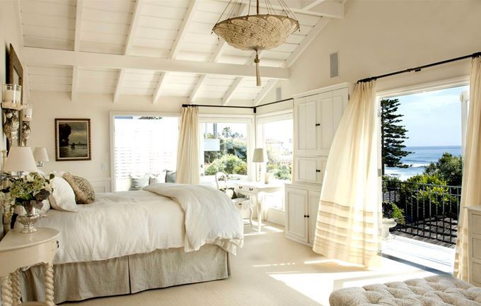 White bedroom with large balcony doors and lots or windows.