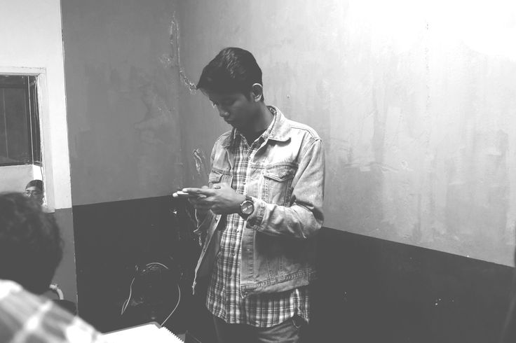 A photo of Emir Oktarianto taken by Ahsani Taqwim while checking his phone before the interview with 8EH Radio ITB.