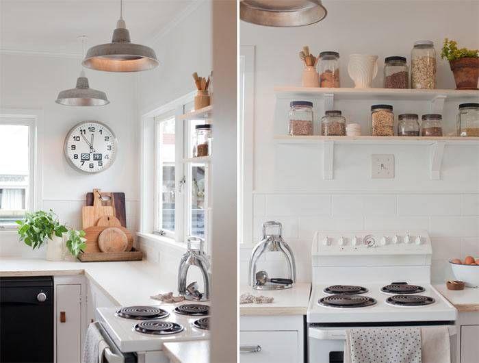 A cozinha de piso de madeira e gabinetes brancos ganhou novos acessórios e uma renovação nos puxadores, luminárias e bancada
