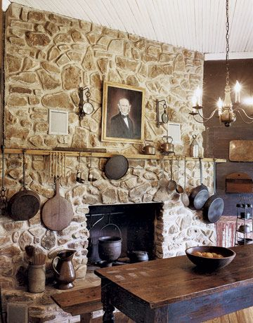 A grand stone hearth sets the tone of this country kitchen and provides a backdrop to display kitchen antiques.
