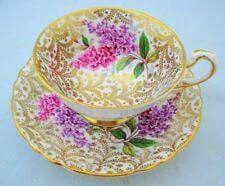Šálek na čaj s podšálkem • zlacený porcelán s malovaným květem šeříku