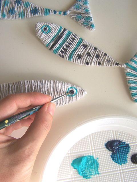 In un piattino di plastica mettete i colori acrilici turchese e blu scuro e decorate a piacere un solo lato dei pesci, se volete appenderli al muro, o entrambi, se volete appenderli mobili al soffitto o ad un lampadario (Foto 6 e 7).