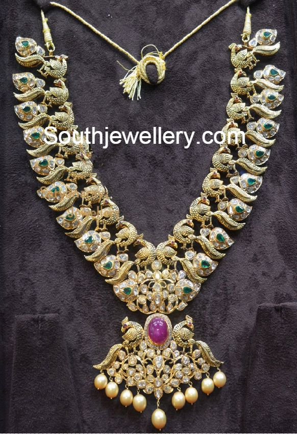 22 carat gold antique finish gorgeous peacock mango pacchi necklace with intricate Nakshi work studded with uncut polki diamonds, emeralds, rubies and south sea pearl drops from P Satyanarayan and Sons Jewellers. For price inquiries contact:Psatyanarayanandsons@gmail.com Phone: +917680944450 Shop Address: P.Satyanarayan & Sons Jewellers Road No.36, Beside ICICI bank, Jubilee Hills, Hyderabad, Andhra Pradesh 500033