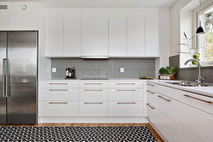 Vitt kök med köksluckan Solid och  rejäla och tåliga arbetsbänkar från Silestone. Infällda spotlights i tak. Komplett utrustat med inbyggnadsugnar, induktionshäll, fläktskåp, kyl och frys. Allt i rostfritt. Diskmaskinen är snyggt integrerad.