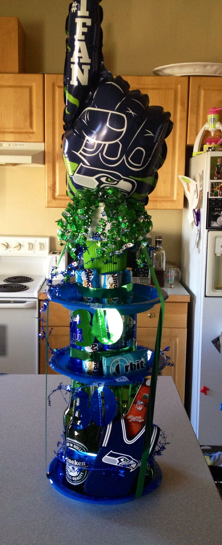 Seahawks Birthday Cake 6 green bottles (beer) 4 cans (blue red bull) 1 cup (topper) 8 mini candy bars (almond joy) 3 blue Plates-make a tower starting with the bottles... Seahawk stuff: beer cozy, Seahawk fan stick (topper) Green & blue ribbon and bows