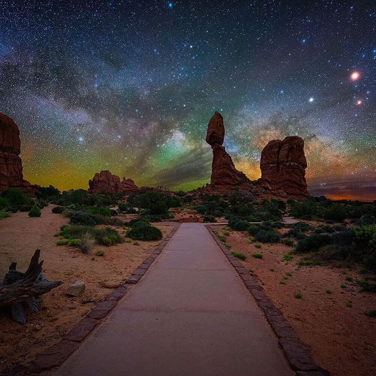 """As the saying goes, """"Half the park is after dark,"""" and nowhere is that more true than at #Arches National Park in Utah. Stay after sunset to see the night sky at Arches come alive with shimmering stars above the colorful red rock formations. Photo of the Milky Way behind Balanced Rock courtesy of Joshua Snow."""