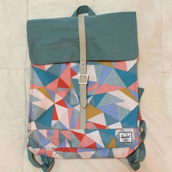 """Herschel City backpack geo print - fits laptop! Awesome Herschel Supply Company backpack with geometric print and blue accents. Rubber strap with a buckle and magnetic closure; one big zippered front pocket, larger open main compartment fits a laptop. Cute red and white lining. Adjustable padded straps. Dimensions 14.25"""" x 12"""" x 2.75"""".  Small spots on inside fold of one side (outside of pack) - see last photo. No trades; Poshmark sales only. Herschel Supply Company Bags"""