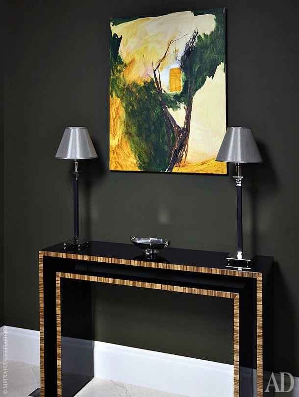 Одна из стен в прихожей зеркальная — это раздвижные двери гардеробной. Остальные стены теплого темно-зеленого оттенка. Из мебели — только консоль + картина. двойная хитрость:  незагроможденная вещами прихожая - как пролог к такому же просторному интерьеру + резкий  переход из темного пространства в светлое уводит внимание от размеров помещения