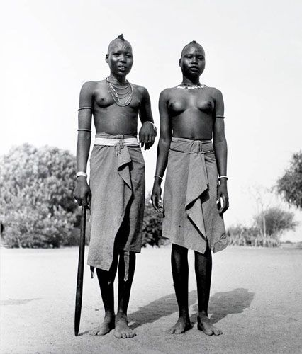 African Dinka girls, by George Rodger, 1948. The Dinka are Sudanese tribespeople who rely on cattle herding at riverside camps in the dry season and grow millet and other grains in fixed settlements during the rainy season